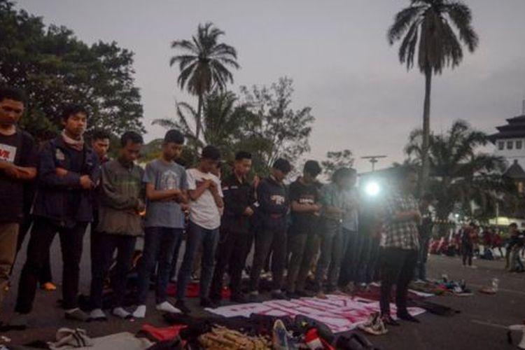 Sejumlah mahasiswa dan pelajar salat Maghrib berjamaah di tengah unjuk rasa di Gedung Sate, Bandung, Sabtu (28/09).