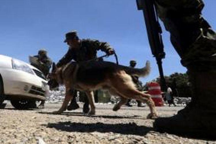 Tentara Meksiko dibantu anjing pelacak memeriksa kendaraan bermotor untuk mencari narkotika. Sejak pemerintah Meksiko mencanangkan perang melawan kartel penyelundup narkotika, sedikitnta 70.000 orang tewas.
