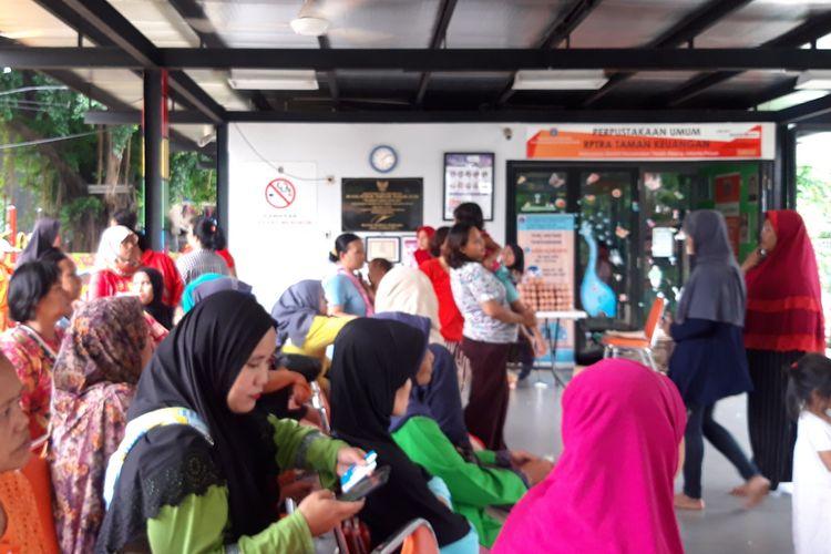 Warga mengantre untuk mengambil pangan murah di RPTRA Keuangan, Bendungan Hilir, Jakarta Pusat, Jumat (5/4/2019)