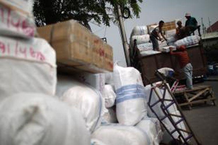 Pekerja memindahkan karung berisi pakaian ke dalam bak truk di salah satu tempat jasa pengiriman paket melalui jalur darat di Jalan Jati Baru, Tanah Abang, Jakarta, Kamis (26/7/2012). Pengiriman barang, terutama yang berisi pakaian jadi, menuju sejumlah kawasan di Pulau Sumatera meningkat hampir dua kali lipat selama bulan ramadhan.