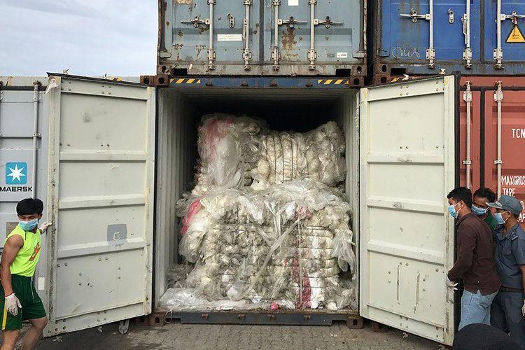 Foto yang dirilis Kementerian Lingkungan Hidup Kamboja, Selasa (16/7/2019), memperlihatkan petugas membuka kontainer berisi sampah plastik di pelabuhan Sihanoukville, Kamboja, yang berasal dari luar negeri.