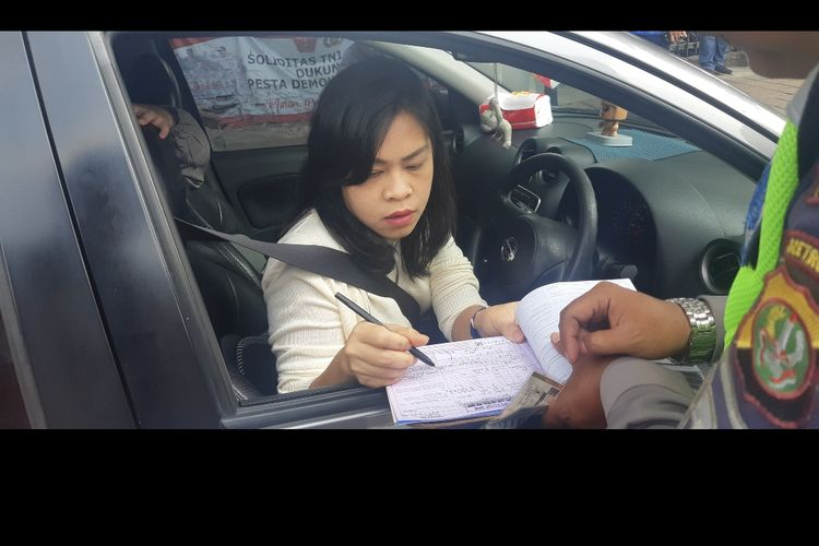 Salah satu pengendara menandatangani surat tilang karena kendaraannya terjaring operasi ganjil genap di Traffic Light Tomang Raya, Jakarta Barat, Senin (9/9/2019).