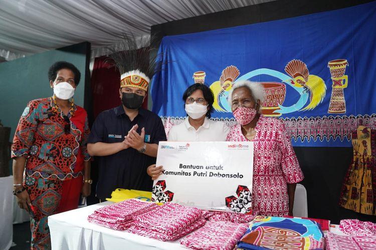 Direktur Consumer Service Telkom Venusiana (kedua dari kanan) menyerahkan simbolis bantuan untuk Komunitas Putri Dobonsolo yang diterima oleh pendiri Batik Papua ?Pondok Putri Dobonsolo? Mariana Ibo (paling kanan) serta disaksikan Menteri BUMN Erick Thohir (kedua dari kiri) dan Ketua Komunitas Seni & Budaya Papua Yakoba Womsiwor (paling kanan) di Jayapura, Minggu (3/10).