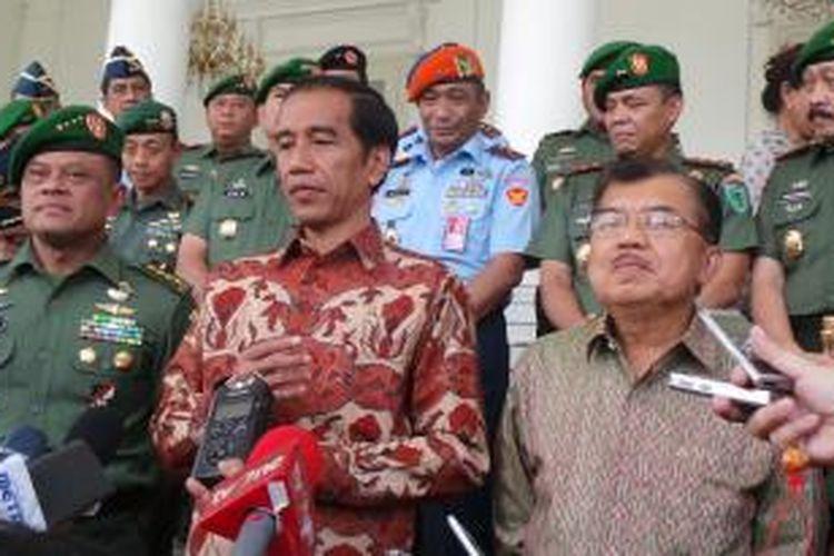 Presiden Joko Widodo (tengah) dan Wakil Presiden Jusuf Kalla (kanan) berbicara kepada wartawan seusai pertemuan dengan para panglima komando daerah militer di Istana Bogor, Jumat (28/11/2014).
