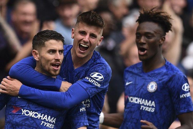 Gelandang Chelsea, Jorginho (kiri), berselebrasi dengan rekannya Mason Mount (tengah) dan Tammy Abraham (kanan), seusai mencetak gol pembuka dalam pertandingan Liga Inggris melawan Brighton and Hove Albion di Stamford Bridge, London, pada Sabtu (28/9/2019).