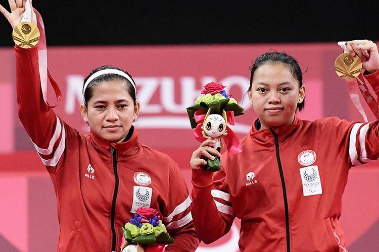 Pebulu tangkis ganda putri Indonesia Oktila Leani Ratri (kiri) dan Sadiyah Khalimatus berpose dengan medali emas saat prosesi penyerahan medali bulu tangkis nomor ganda putri kategori SL3-SU5 pada Paralimpiade Tokyo 2020 di Yoyogi National Stadium, Tokyo, Jepang, Sabtu (4/9/2021). Leani/Khalimatus meraih medali emas setelah mengalahkan wakil China Cheng He Fang-Ma Huihui dengan skor 21-18 dan 21-12.