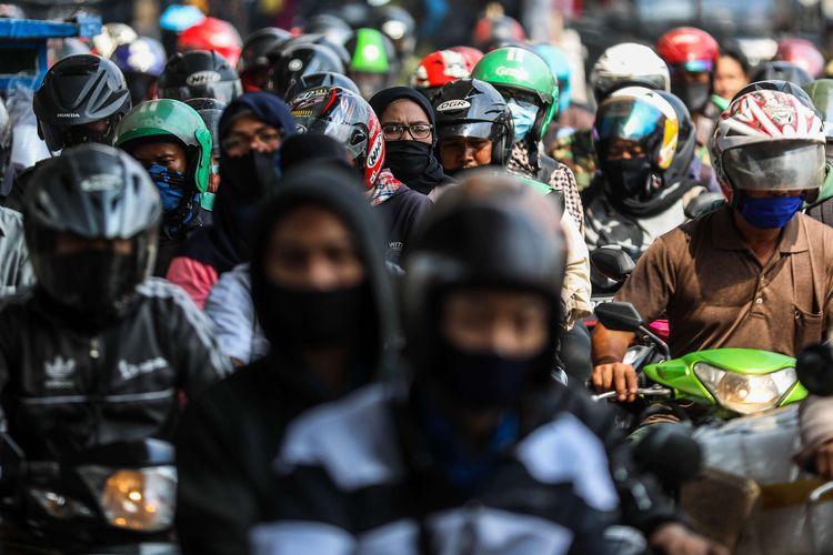 Pengguna kendaraan bermotor menggunakan masker saat melintasi rel kereta di Jalan Tanjung Selor, Grogol, Jakarta Barat, Senin (24/8/2020). Gubernur DKI Jakarta Anies Baswedan memutuskan untuk kembali memperpanjang pembatasan sosial berskala besar (PSBB) yang keempat kalinya terhitung mulai Jumat (14/8/2020) sampai 27 Agustus 2020.