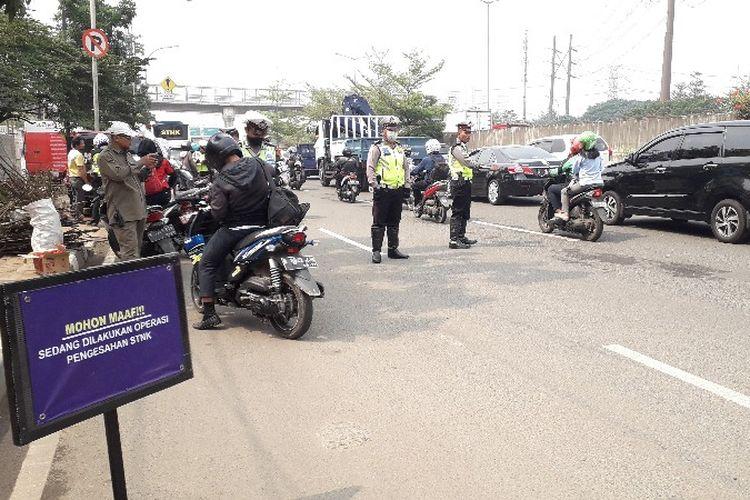Samsat Jakarta Barat menggelar operasi razia gabungan pengesahan surat tanda nomor kendaraan (STNK) dan pembayaran pajak kendaraan di Jalan Lingkar Luar Barat, Cengkareng, Jakarta Barat pada Kamis (27/9/2018).