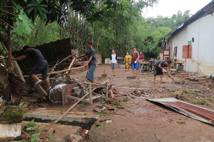 Warga Desa Banjaragung, Kecamatan Bareng, Kabupaten Jombang, Jawa Timur, membersihkan sampah sisa banjir serta memperbaiki rumahnya yang rusak akibat bandang, Selasa (2/2/2021).