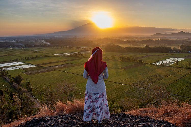 Seorang pengunjung berfoto dengan latar belakang matahari terbit di Gunung Pegat Sukoharjo.