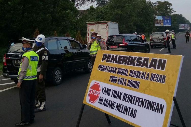 Petugas gabungan sedang melakukan pemeriksaan kendaraan yang melintas di pintu Tol Jagorawi di hari pertama penerapan pembatasan sosial berskala besar (PSBB) Kota Bogor, Rabu (15/4/2020).