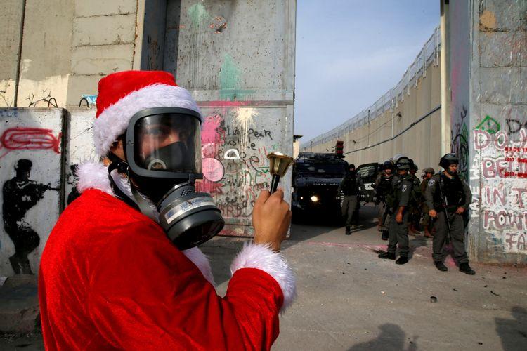 Warga Palestina mengenakan kostum Santa Claus, Sabtu (23/12/2017), berdiri di depan pasukan tentara Israel dengan memasang masker anti-gas air mata, di Betlehem, Yerusalem, sebagai bentuk protes terkait pernyataan Presiden Amerika Serikat Donald Trump yang mengakui Yerusalem sebagai ibu kota Israel.