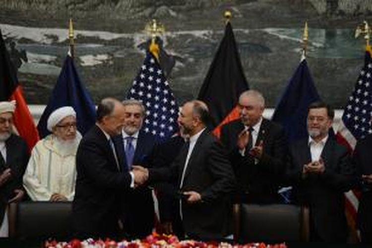 Penasihan keamanan Afganistan Hanif Atmar (kanan) berjabat tangan dengan Dubes AS untuk Afganistan James Cunningham setelah menandatangani pakta keamanan AS-Afganistan yang sempat tertunda di saat-saat terakhir masa pemerintahan Presiden Hamid Karzai.