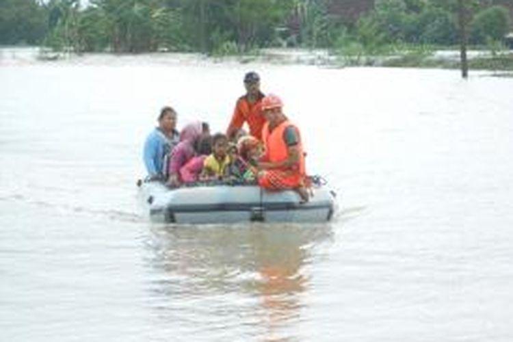 Tim sar mengevakuasi warga Desa Tedunan Kecamatan Wedung, Demak yang terisolir akibat banjir setinggi 1,5 meter, Rabu (22/1/2014)