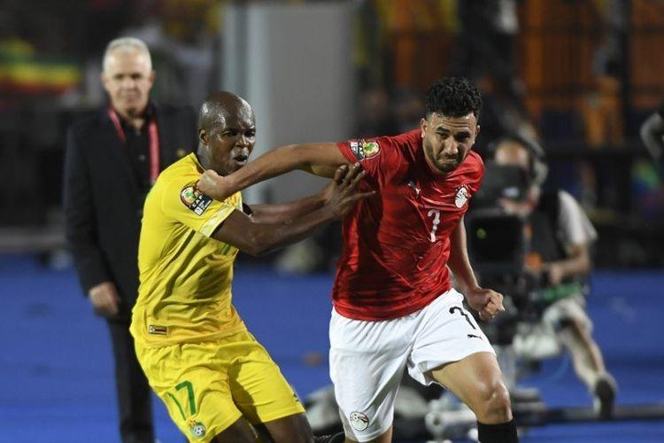 Mahmoud Trezegut Hassan mencoba melewati penjagaan lawan pada pertandingan Mesir vs Zimbabwe dalam partai pembuka Piala Afrika 2019 di Kairo, 21 Juni 2019.