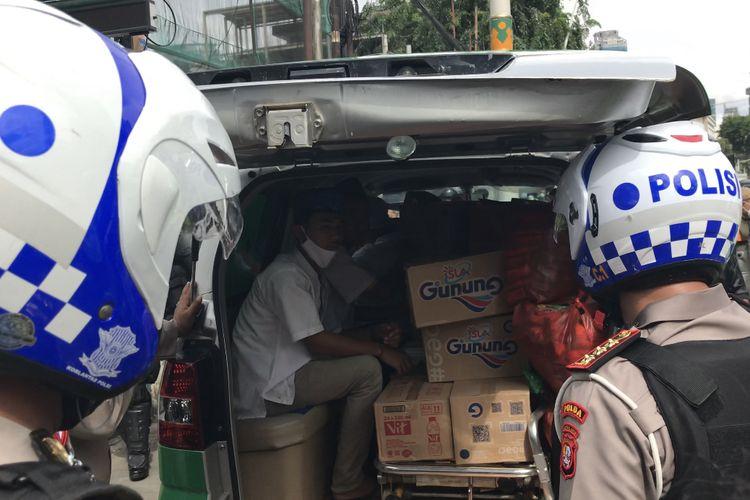 Aparat kepolisian saat memeriksa dan mengamakan satu mobil ambulans berisi logistik berupa makanan dan minuman di Jalan Jatibaru, Tanah Abang, Jakarta Pusat pada Jumat (18/12/2020) siang.