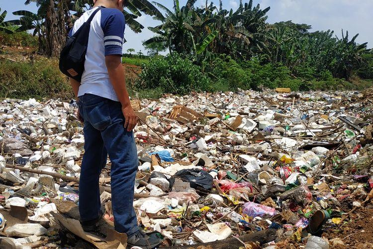 Warga berdiri di atas tumpukan sampah yang memenuhi aliran Kali Jambe di Desa Satriajaya, Tambun Utara, Kabupaten Bekasi, Rabu (30/10/2019) siang.