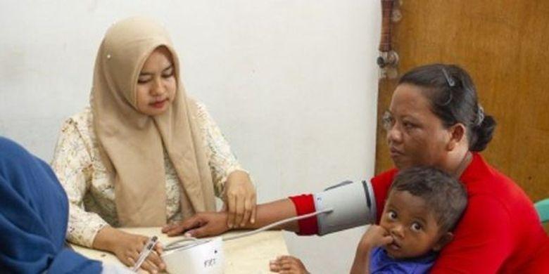 Seorang perawat memeriksa kesehatan warga di Posko Pelayanan Kesehatan PHE ONWJ, Cemarajaya, Karawang, Jawa Barat, Selasa (30/07).