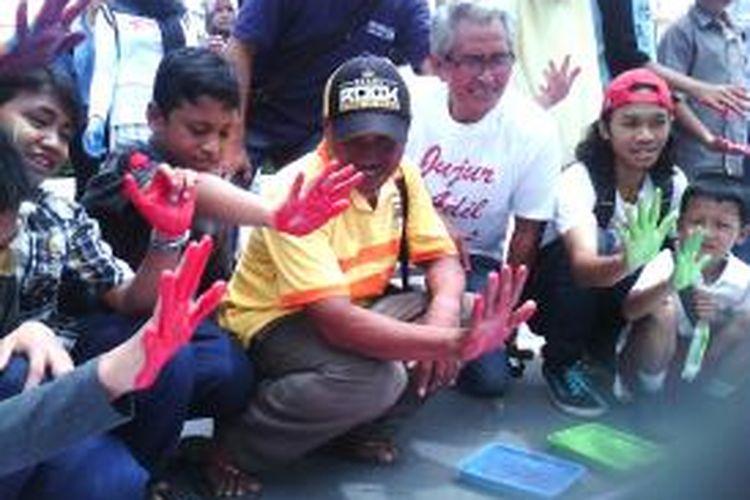 Pong Harjatmo saat aksi membubuhkan cap tangan di titik nol km yogyakarta