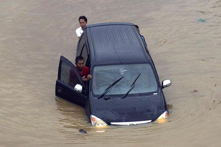 Luapan Kali Ciliwung memutus jalur kendaraan di Jalan KH Abdullah Syafiie, Tebet, Jakarta Selatan, Senin (13/1/2014). Luapan kali mulai menggenangi permukiman dan memutus jalan sejak Senin dini hari.