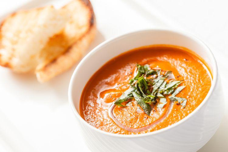 Ilustrasi sup krim tomat yang disajikan dengan roti panggang.