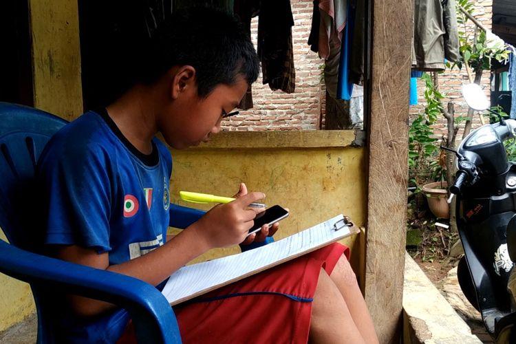 Jonathan (13) pelajar SMP di Bandar Lampung sedang memahami soal dari pembelajaran daring kelasnya, Kamis (6/8/2020). Untuk memenuhi kebutuhan kuota internet, Jonathan berjualan pempek di sekitar kampung.
