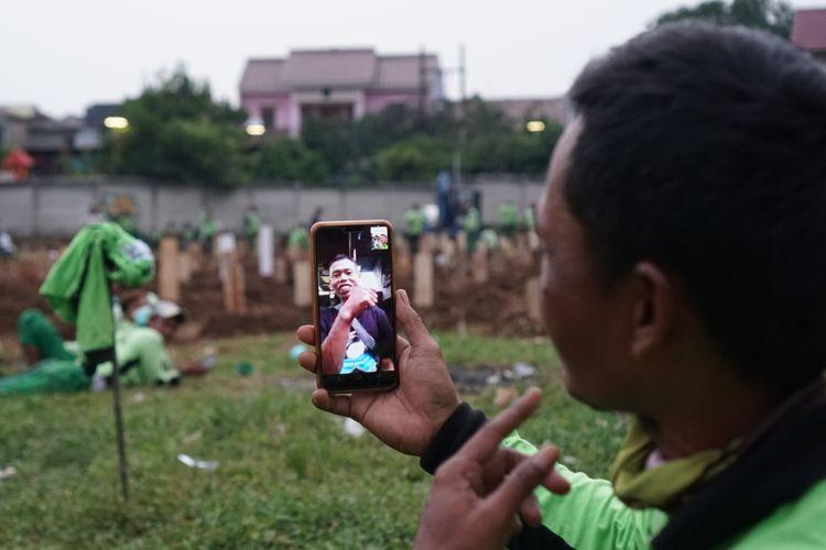 Para penggali kubur melakukan panggilan video sembari menunggu peti jenazah pasien Covid-19 datang di Taman Pemakaman Umum (TPU) Srengseng Sawah, Jagakarsa, Jakarta Selatan pada Jumat (15/1/2021). TPU Srengseng Sawah dijadikan sebagai tempat pemakaman jenazah pasien Covid-19 sejak Selasa (12/1/2021). TPU Srengseng Sawah memiliki lahan seluas 0,5 hektar dan bisa menampung sekitar 700 makam untuk jenazah pasien Covid-19.