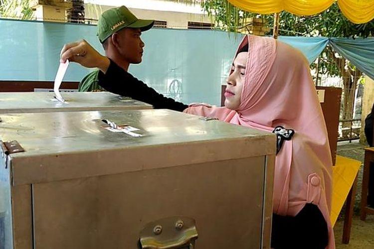 Seorang warga sedang memasukkan kertas suara di TPS 2 Gampong Nusa, Kecamatan Lhoknga Kabupaten Aceh Besar. Warga ini memilih Bupati Kabupaten Aceh Besar dan Gubernur Aceh beserta wakilnya, pada pilkada langsung 2017..