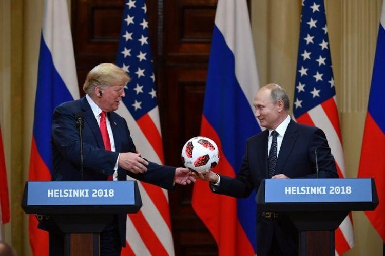 Presiden Rusia Vladimir Putin memberikan bola Piala Dunia 2018 ke Presiden Amerika Serikat Donald Trump pada konferensi pers bersama usai pertemuan di Istana Presiden di Helsinki, Finlandia, Senin (16/7/2018). (AFP/Yuri Kadobnov)
