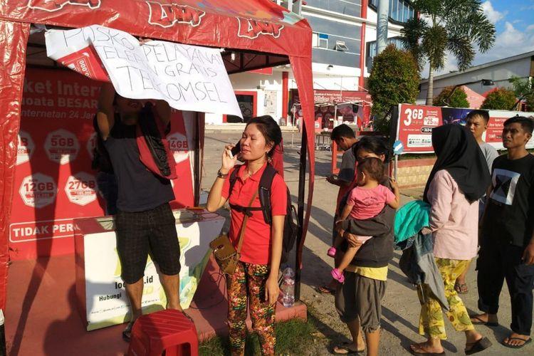 Layanan telepon gratis yang disediakan Telkomsel di halaman Grapari di Palu, pasca-gempa bumi dan tsunami.