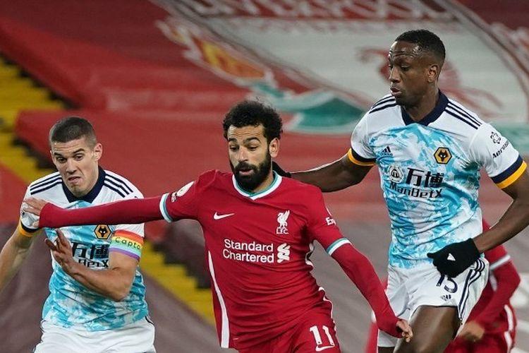 Mohamed Salah berebut bola dengan Conor Coady dan Willy Boly dalam laga Liverpool vs Wolves. Pertandingan pekan ke-11 Liga Inggris 2020-2021 yang digelar di Stadion Anfield, Minggu (6/12/2020), itu berakhir dengan kemenangan bagi Liverpool.
