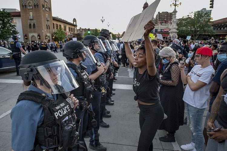 Dalam foto 29 Mei 2020 ini, seorang wanita memegang plakat unjuk rasa ketika dia berteriak Anda tidak punya wewenang untuk membunuh kaum minoritas, di Kepolisian Kota Kansas selama protes melawan kebrutalan polisi dan kematian George Floyd di Country Club Plaza di Kota Kansas.