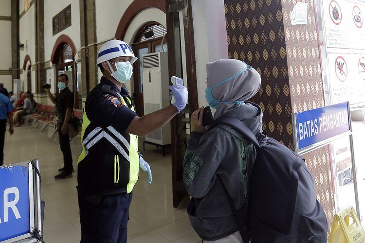 Salah seorang petugas sedang menunjukkan suhu tubu kepada calon penumpang moda tranportasi massal.