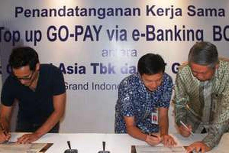 Direktur PT Bank Central Asia Tbk (BCA) Suwignyo Budiman (kanan), Direktur BCA Armand W. Hartono (tengah) dan CEO PT GO-JEK Indonesia (GO-JEK) Nadiem Makarim (kiri) menandatangani Perjanjian Kerja Sama yang menandai dukungan penuh BCA melalui fasilitas kemudahan Top Up GO-PAY sebagai solusi cash management bagi pelanggan dan mitra driver GO-JEK di Jakarta (17/5/2016).