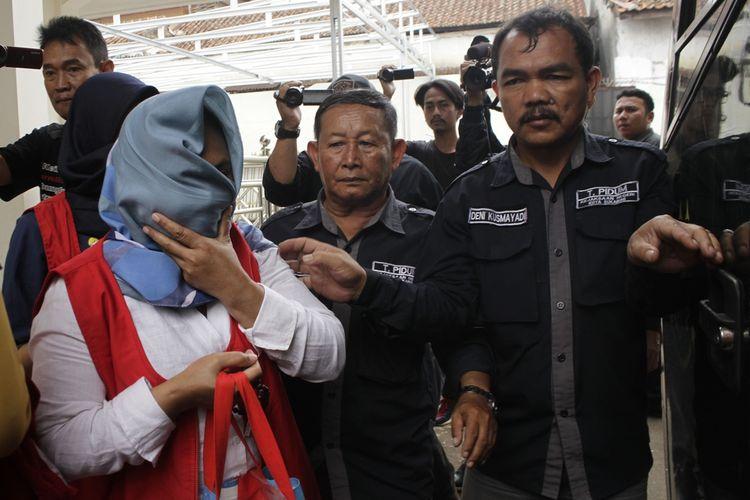 Terdakwa SR alias Yuyu (kiri) didampingi dua petugas Kejaksaan Negeri (Kejari) Sukabumi saat akan menaiki mobil tahanan setelah sidang di Pengadilan Negeri (PN) Sukabumi, Jawa Barat, Selasa (10/12/2019).