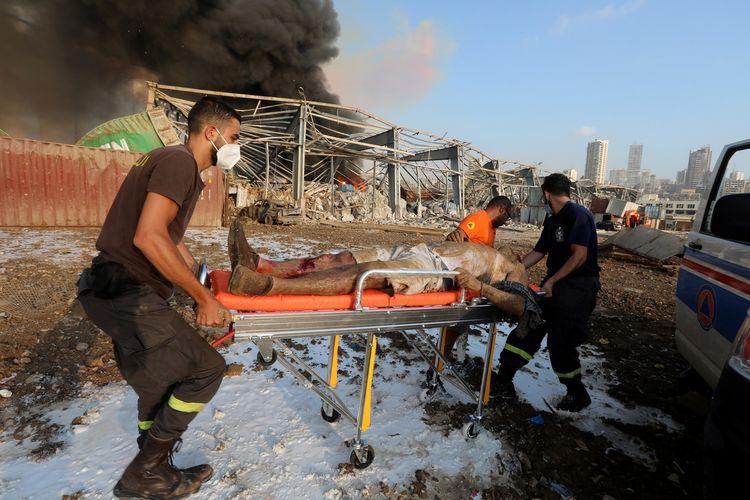 Seorang warga yang terluka diangkut menggunakan brankar oleh petugas penyelamat setelah dua ledakan yang mengguncang Beirut, Lebanon, pada 4 Agustus 2020.