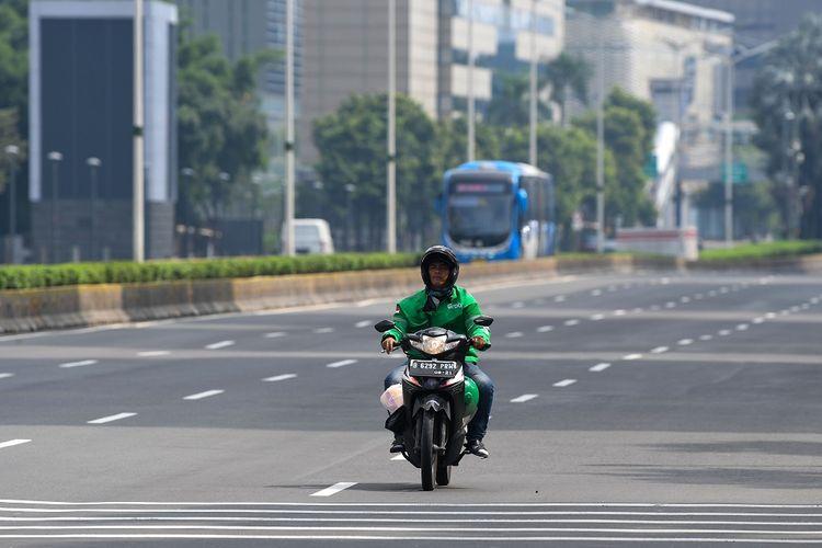 Pengendara ojek daring melintasi jalan MH Thamrin, Jakarta, Minggu (29/3/2020). Pemprov DKI Jakarta melakukan pembatasan aktivitas di Ibu Kota dengan memperpanjang masa tanggap darurat COVID-19 hingga 19 April 2020 sehubungan dengan meluasnya pandemi COVID-19. ANTARA FOTO/M Risyal Hidayat/pras.