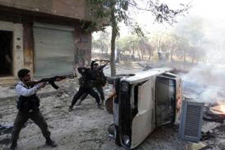 Pasukan pemberontak Suriah berlindung di balik sebuah bangkai mobil sambil melepaskan tembakan dalam pertempuran di distrik Salaheddin, Aleppo. Kelompok Human Right Watch (HRW) dalam laporan terbarunya mengatakan pasukan pemberontak membunuh ratusan warga sipil sepanjang Agustus lalu.