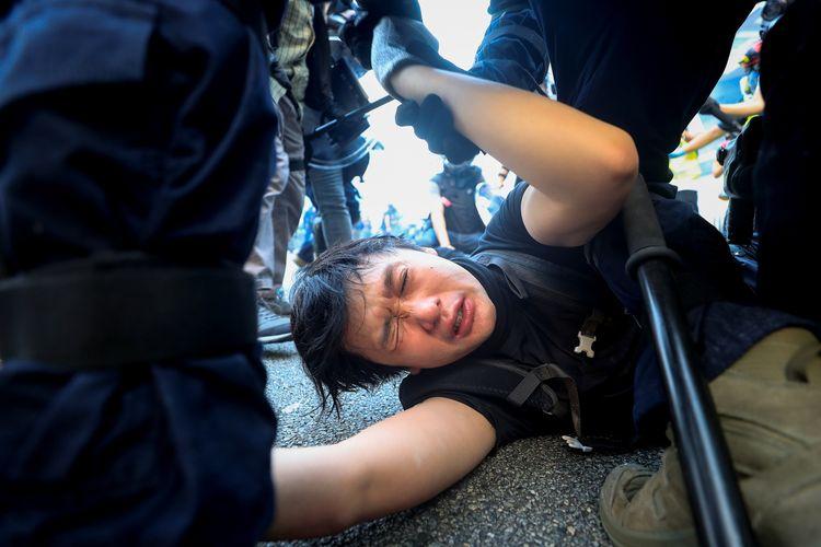 Seorang pengunjuk rasa anti-pemerintah ditahan saat reli di Hong Kong, China, Minggu (29/9/2019). Foto diambil tanggal 29 September 2019.