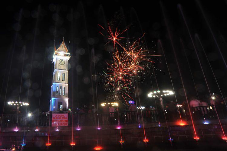 Pengunjung menyaksikan kembang api yang dinyalakan saat malam pergantian tahun, di kawasan Jam Gadang, Bukittinggi, Sumatera Barat, Rabu (1/1/2020). Meskipun ada imbauan dilarang menyalakan kembang api dan terompet dari Pemda setempat, namun pengunjung tetap memadati kawasan objek wisata tersebut menyambut tahun baru 2020.