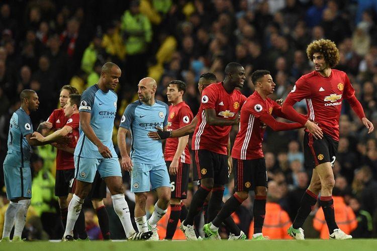 Gelandang Manchester United, Marouane Fellaini (kanan), meninggalkan lapangan setelah menerima kartu merah dalam pertandingan Premier League melawan Manchester City di Stadion Etihad, pada 27 April 2017.