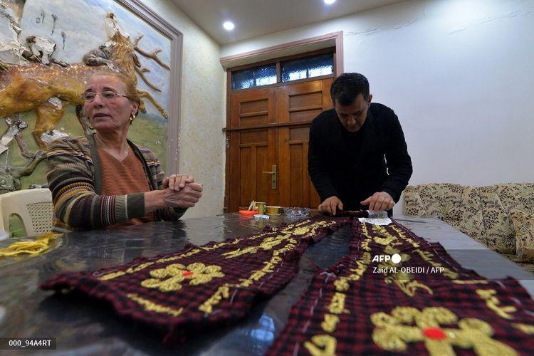 Ammar Yaqo melihat saat Karjiya Baqtar menyulam stola yang menggunakan benang emas, untuk diberikan kepada Paus Fransiskus selama kunjungannya yang akan datang ke kampung halamannya di Qaraqosh, Irak. pada 4 Maret 2021. Stola sepanjang dua meter itu seluruhnya diproduksi secara lokal, dari kain kotak-kotak merah dan hitam hingga doa Syriac yang dijahit tangan di sepanjang tepinya dengan emas berkilauan. Ini dirancang oleh Ammar Yaqo, pendeta di Gereja Al-Tahera di Qaraqosh.