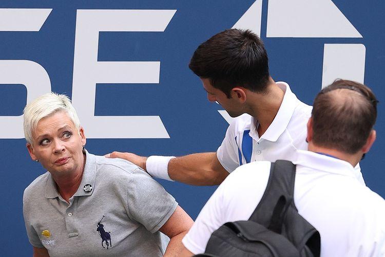 Petenis Novak Djokovic (baju putih) dan hakim garis (kiri) yang terkena pukulan bola dalam laga keempat saat melawan Pablo Carreno Busta dari Spanyol pada US Open 2020 di USTA Billie Jean King National Tennis Center pada 6 September 2020.
