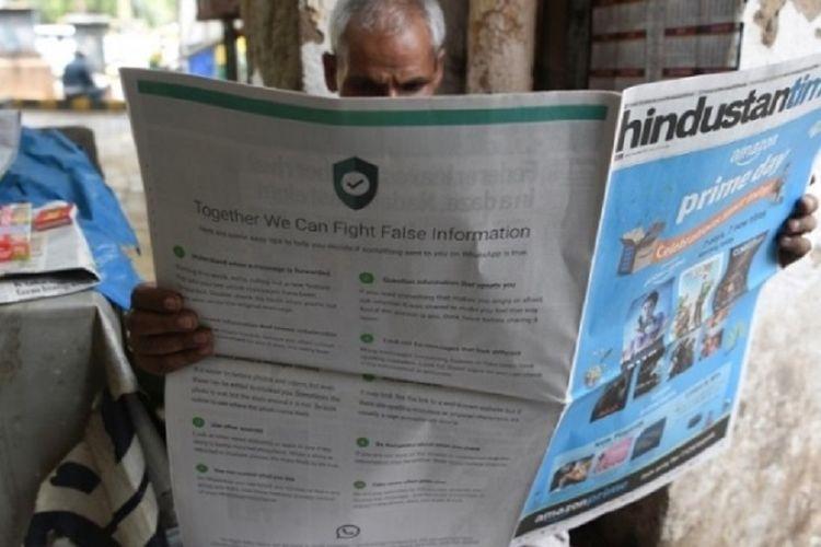Seseorang sedang membaca koran dengan iklan WhatsApp untuk perangi hoaks tampil satu halaman penuh di bagian belakang.