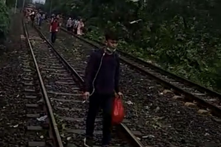 Penumpang KRL berjalan kaki di tengah rel setelah kereta tak bisa melintas di Kebayoran Lama akibat ada pohon tumbang pada Minggu (11/4/4/2021).
