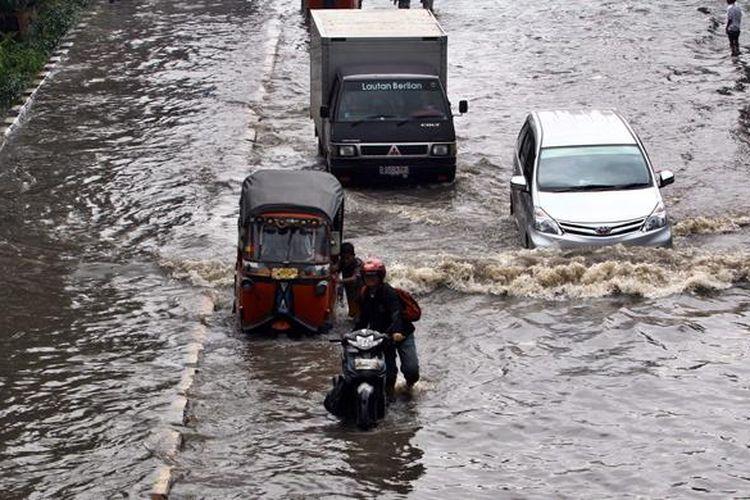 Sejumlah kendaraan melintasi banjir yang menggenangi Jalan Gunung Sahari Raya, Pademangan, Jakarta Utara, Jumat (17/1/2014). Hujan lebat yang mengguyur Jakarta sejak pagi, membuat jalan tersebut tergenang dan diperparah sistem drainase yang kurang baik.