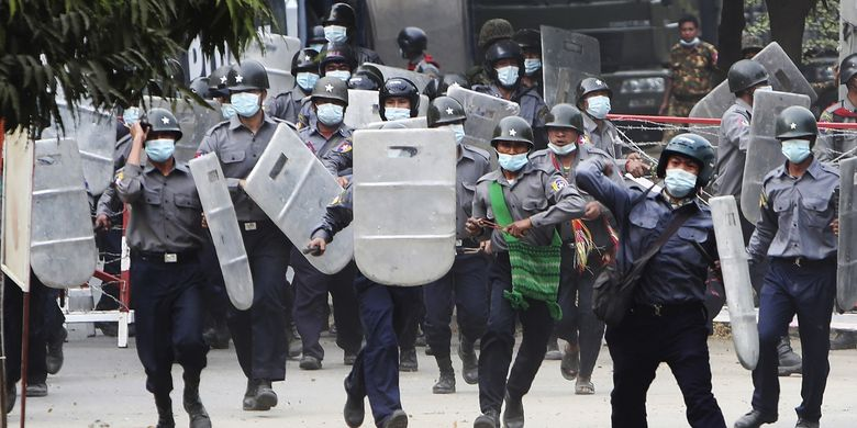 Police charge forward to disperse protesters in Mandalay, Myanmar on Saturday, Feb. 20, 2021. Security forces in Myanmar ratcheted up their pressure against anti-coup protesters Saturday, using water cannons, tear gas, slingshots and rubber bullets against demonstrators and striking dock workers in Mandalay, the nation's second-largest city. (AP Photos)
