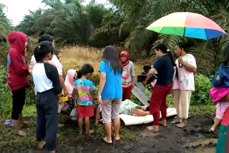 Sejumlah ibu-ibu membantu Wahyuni (38) saat melahirkan bayi di jalan berlumpur di Kepenghuluan Sungai Sanggam, Kecamatan Limau Kapas, Kabupaten Rohil, Riau, Kamis (24/9/2020).