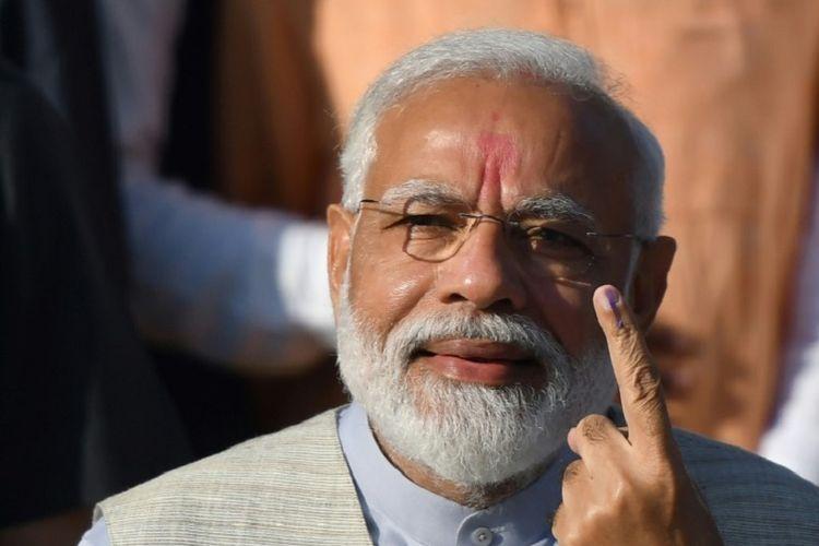 Perdana Menteri India Narendra Modi menunjukan jari tangannya yang telah tercelup tinta setelah memberikan suaranya di TPS di Ahmedabad, negara bagian Gujarat, Selasa, 23 April 2019