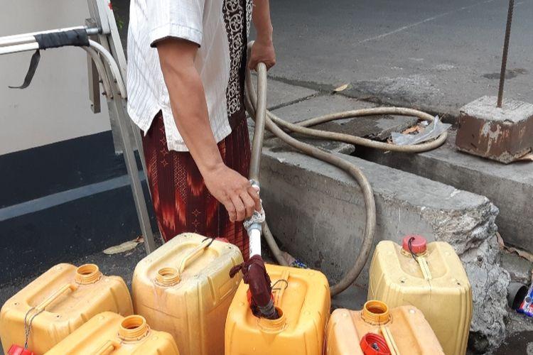 Saiful Anwar (40) sedang mengisi air PAM dalam dirigen sebab kelangkaan air bersih yang sudah melanda warga RW 09, Kelurahan Pegadungan, Kalideres, Jakarta Barat, Kamis (19/9/2019)